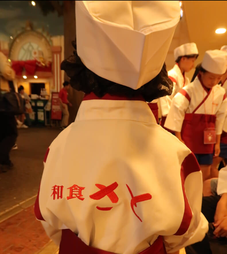 和食さとロゴ入りの制服を着たとらクンの後ろ姿